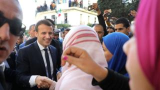 French President Emmanuel Macron greets people in the streets of Algiers on December 6, 2017. Macron began his first official trip to Algeria, announcing that he was visiting as a 'friend' despite France's historically prickly relationship with its former colony.