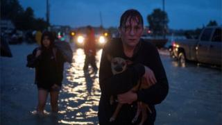 A woman holds her dog as she goes to higher ground after evacuating her home due to floods caused by Tropical Storm Harvey in east Houston.