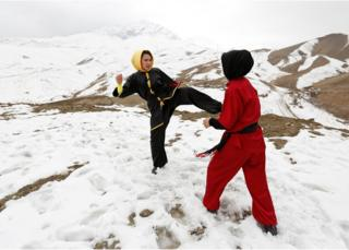 Sima Azimi, a trainer at the Shaolin Wushu club, and Shakila Muradi, show their Wushu skills to other students on a hilltop in Kabul, Afghanistan.