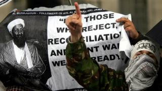 A demonstrator protests next to a banner of the contoversial Islamic group Al-Muhajiroun, depicting Osama Bin Laden, outside Downing Street, London, May 4, 2004.