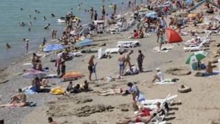Tourists sunbathing on a sandy beach in Crimea