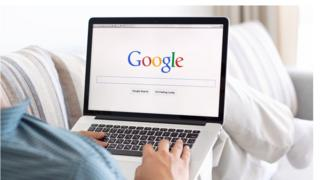 A laptop shows the Google search engine