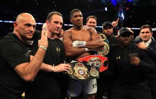 Anthony Joshua en un ring rodeado de entrenadores y con el cinturón de campeón.
