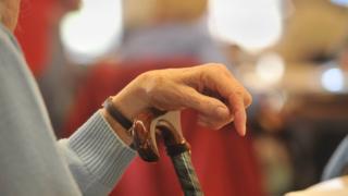 An elderly woman leaning on a walking stick