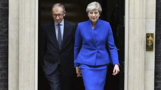 Theresa May heads out of Downing Street on her way to see the Queen