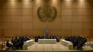 The assembled delegates face each other across a grand chamber, beneath the United Nations symbol