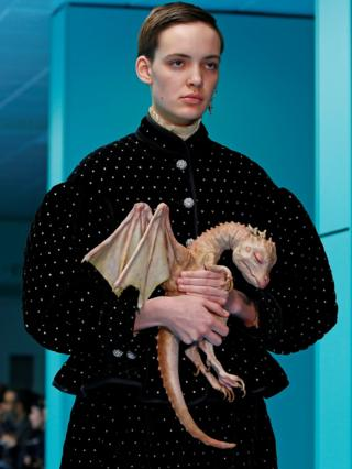 A female model on the catwalk clutching a prosthetic sleeping baby dragon
