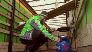イケア・トラックの荷台で食事の準備をする運転手のクリスチャンさん