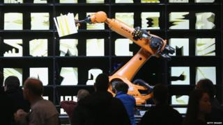 A Kuka robot performs as part of the Robochop interactive robot installation at the 2015 CeBIT technology trade fair