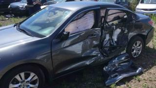 Picture of the damaged car after it was hit by a truck