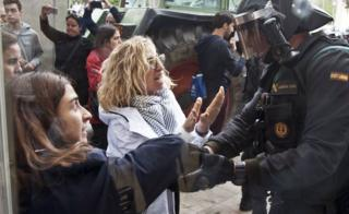 Two women argue with a Spanish National policeman during clashes between Catalan pro-independence people and police forces