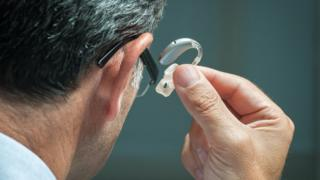 A man putting in his hearing aid