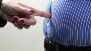 Палец упирается в живот толстяка