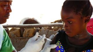 Ugandan girl being given HPV vaccine funded by UK aid.