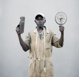 A young man holds up his tools.