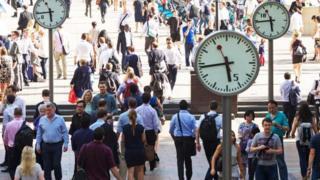 Personas caminando una plaza con varios relojes