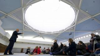 People listen to the explanations of guide Mohamed Latahi (L), as they visit the Strasbourg Grand Mosque during an open day weekend for mosques in France
