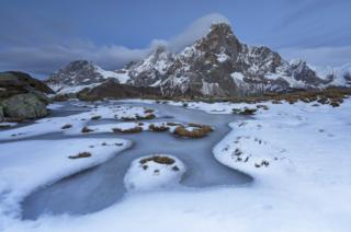 A frozen pond with mountains behind