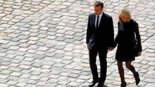 Mr Macron and his wife Brigitte holding hands