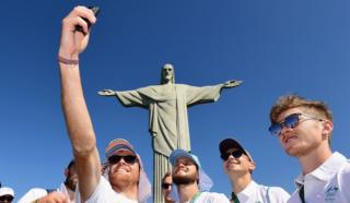 Jake Whetton of the Australian Men's Hockey team takes a photo of himself and team mates in front of the Christ the Redeemer statue on August 1, 2016 in Rio de Janeiro, Brazil.
