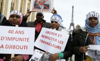 """Djiboutian holding placards reading (L-R): """"40 years of impunity in Djibouti"""" and """"Free and respect workers"""" in Paris, France - Saturday 25 February 2017"""