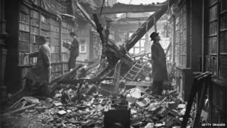 Men look at books in bomb damaged library