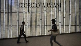 People walking past a store of top Italian designer Giorgio Armani in Hong Kong