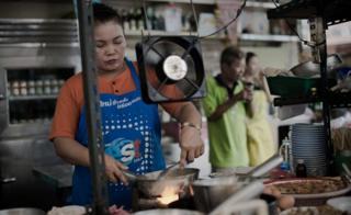 A woman works in restaurant kitchen in Thailand
