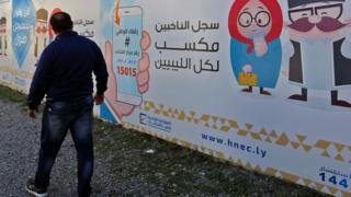 Man stands in front of Libyan election poster
