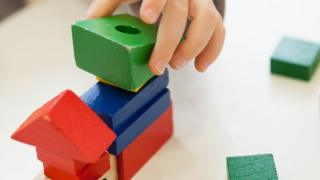 Child's hand playing with coloured wooden brick shapes on white table