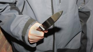Teenage boy holding a knife