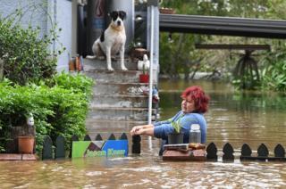 Una mujer intenta alcanzar su case meintras su perro la observa, en la región central de Lismore, Nuevo Gales Sur, Australia, 31 marzo de 2017.