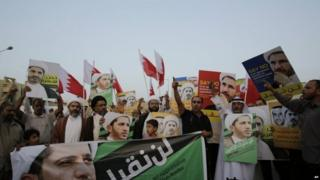Men and boys chant slogans and raise national flags and posters of Sheikh Ali Salman during a protest in Bahrain on 16 June 2015