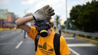 Opositor venezolano con máscara y guantes