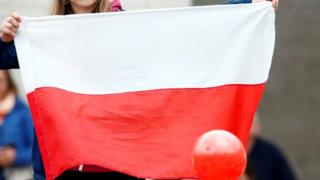 Woman holding a Polish flag