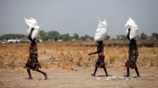 "Three women carry a sack of food distributed on March 4, 2017, in Ganyiel, Panyijiar county, in South Sudan. South Sudan was declared the site of the world""s first famine in six years, affecting about 100,000 people."