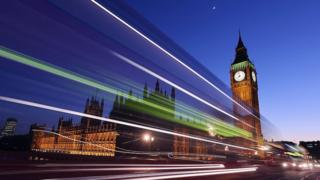 A bus travels along Westminster Bridge past the Houses of Parliament