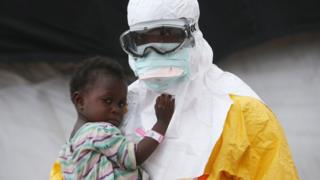 A man in a protective suit holding a child