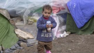 A toddler of a migrant family holds a baby bottle with milk at a makeshift camp in Idomeni, Greece. Photo: 18 March 2016