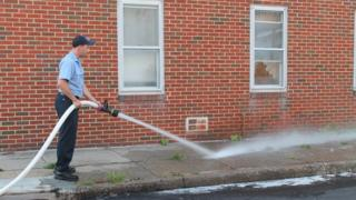 A Baltimore firefighter washes blood off of the sidewalk