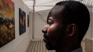 """Senegalese artist Baba Ly was one of dozens of artists to present at one of the Dakar Biennale's """"Off"""" sites. Here he stands amid paintings from his series on urbanism."""
