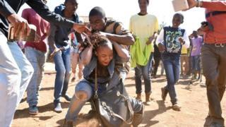 Bw. Mnguni anaonekana akitafuna nywele za mwanadada huyu katika mojawepo ya mahubiri yake Afrika Kusini mwaka 2015