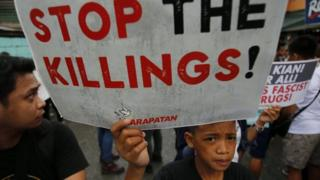 A Filipino sympathiser holds a placard while joining the funeral for student Kian Delos Santos, on a street in Manila, Philippines, 26 August 2017