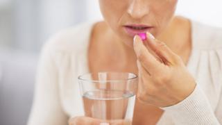 A woman taking a pill