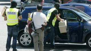 Police officers take away material seized during the raid