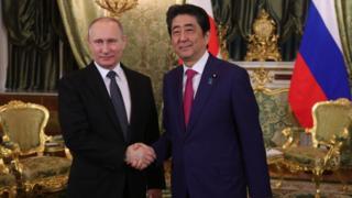 クレムリンで握手するプーチン大統領と安倍首相(27日)