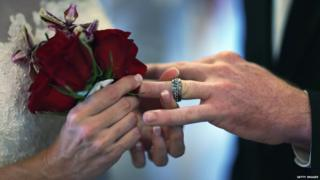 "Luanne Round slips a ring on the finger of her husband Matthew Round as they are wed during a group Valentine""s day wedding at the National Croquet Center on February 14, 2013 in West Palm Beach, Florida."