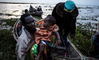 Internally displaced Congolese return to the shore line of lake Albert after spending the night out in the lake for safety on March 05, 2018 in Tchomia. Displaced Congolese, fleeing inter-communal violence in the Ituri region of the Democratic Republic of the Congo, make their way to the Tchomia on the DRC side of Lake Albert in search of safety and boats to make the crossing to the safety of the refugee camps in Uganda