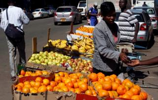 A woman buys oranges from a street vendor in central Harare, Zimbabwe
