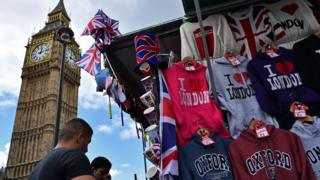 Tourists look at London themed merchandise with Big Ben in background